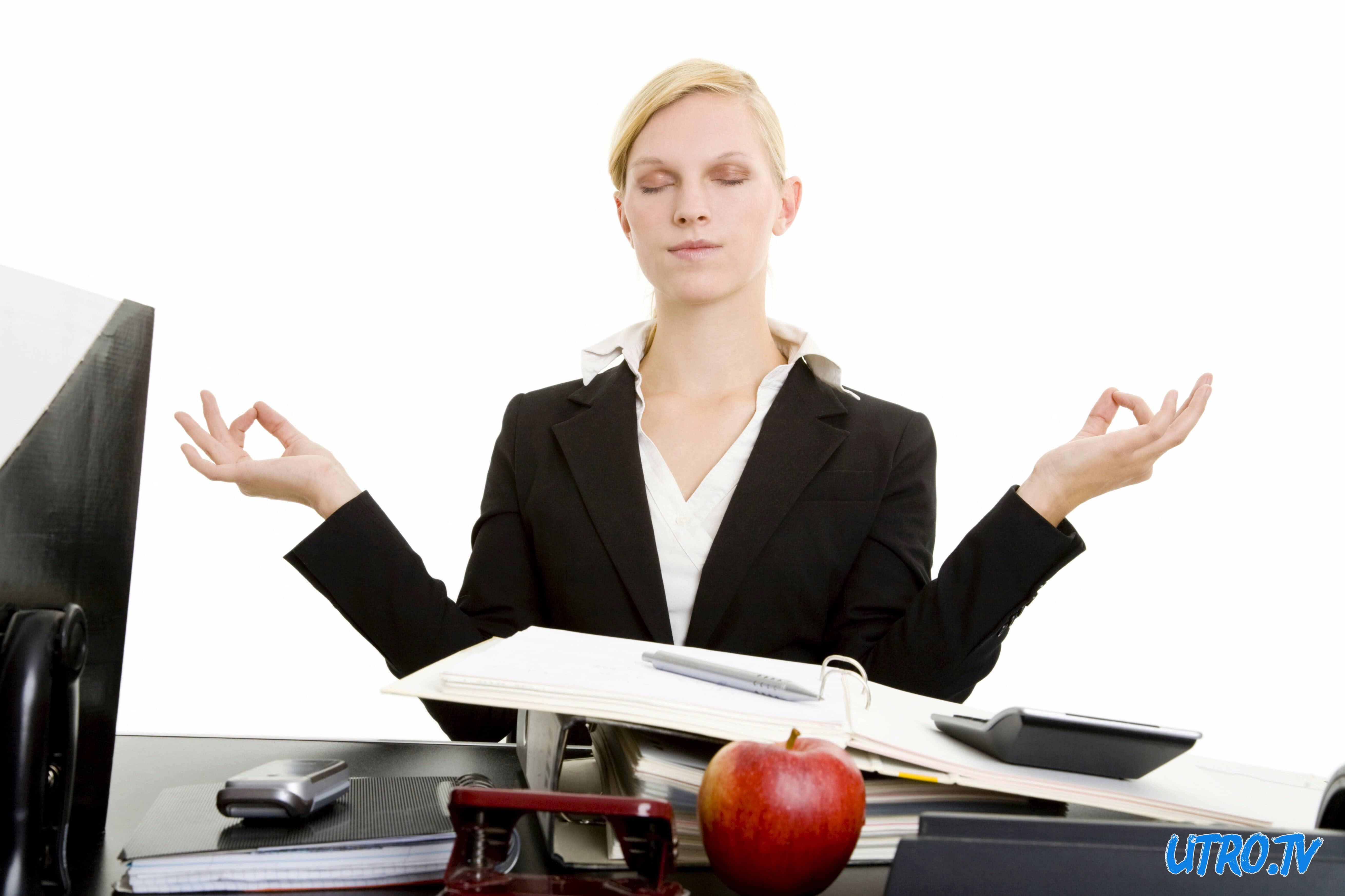 Blond businesswoman meditating at her desk