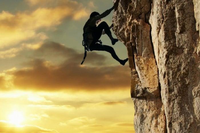 мужчина взбирается на гору