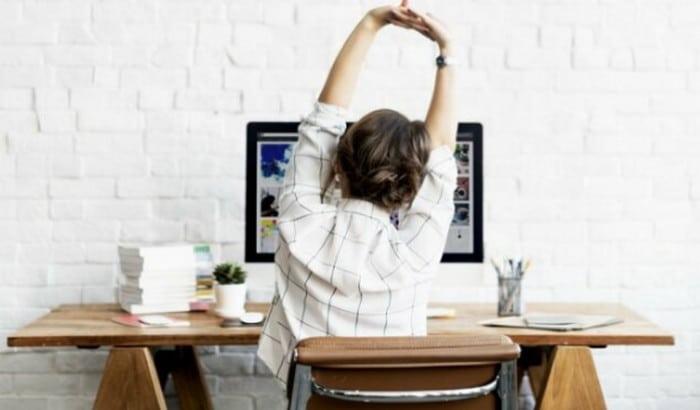девушка потягивается возле компьютера