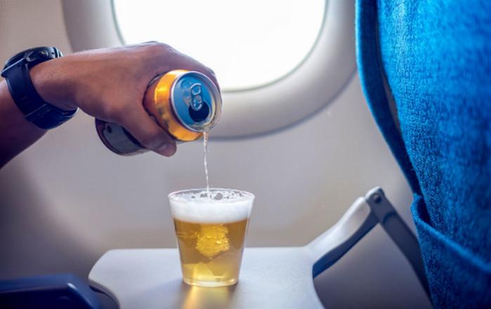 пьет пиво в самолете